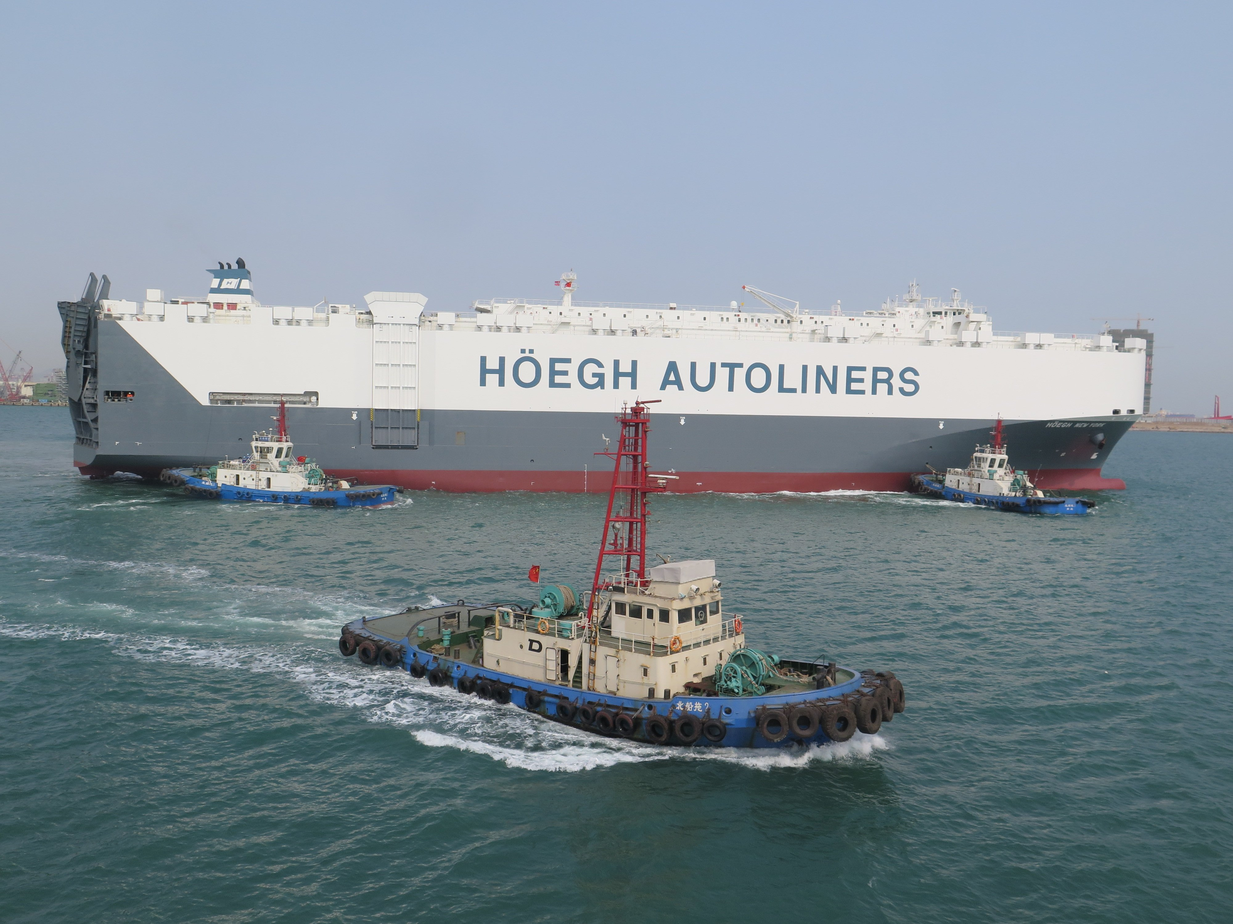 Höegh New York being escorted by tugs on her way out of the dock.